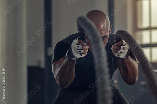Cuadros en Lienzo  Black man doing intensive battle rope workout