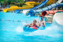 In The Summer, On A Bright Sunny Day, In A Water Park, Father And Daughter Slide Down The Hill.