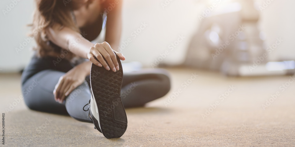Fototapeta Beautiful Asian woman with tan and slim body stretching legs before exercise