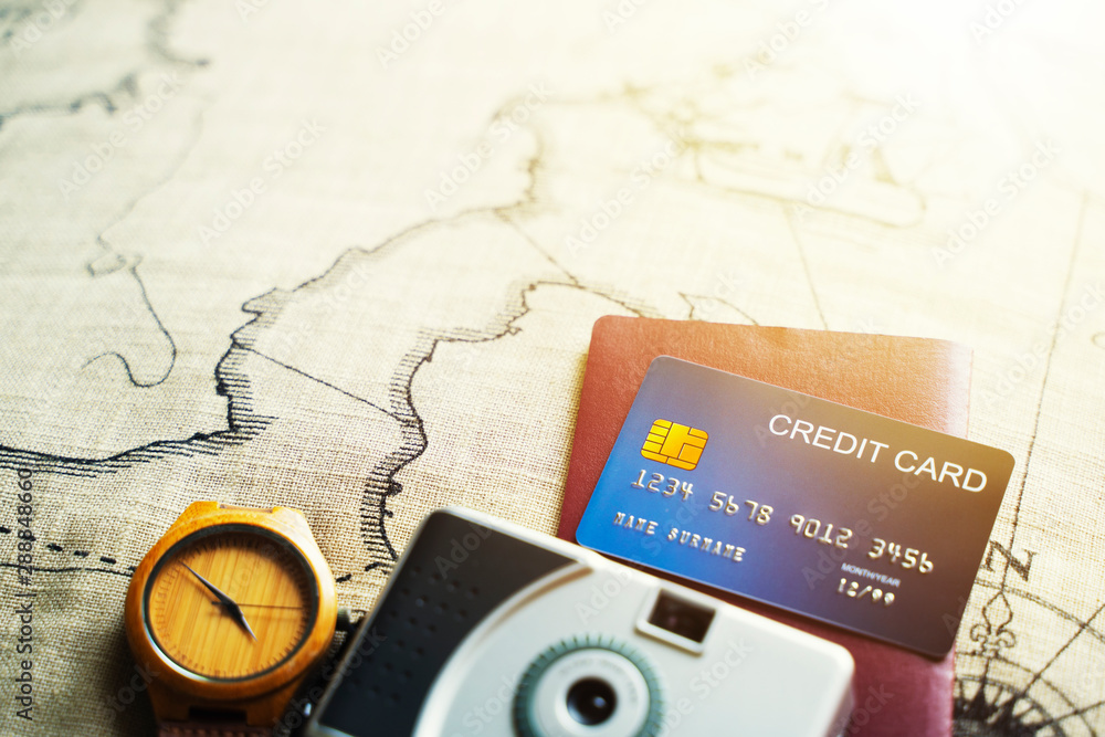 Fototapeta Credit card, passport, camera and vintage watch on old map with free space for text. Travel and business background.
