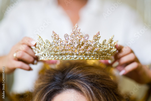girl puts crown jewelry on the bride s head. close up Canvas Print