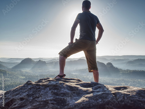 Photo  Sports man in outoor clothes and boots walking on rocky peak.