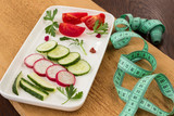 Fototapeta Tęcza - Vegetables in a ceramic plate on an uncouth board. Measuring tape. Low calorie diet concept.