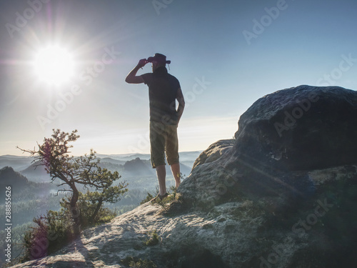 Trekker in cowboy hat on mountain with Sunrise enjoy view Wallpaper Mural