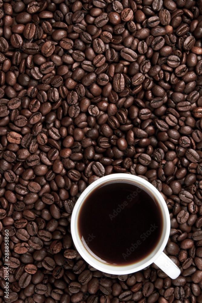 Fototapeta Coffee beans surrounding a coffee mug
