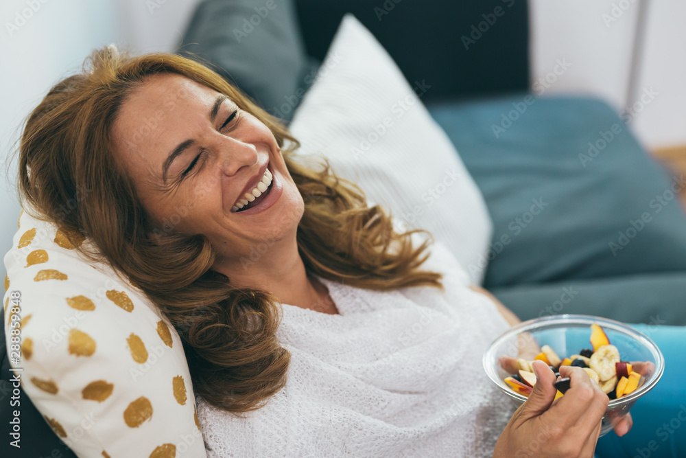 Fototapeta mature woman sitting sofa and eating fruit salad at her home