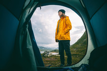 Wild Camping. View From The Tourist Tent To The Mountains In Jutunheimen Park In Norway, Girl Traveler In A Yellow Jacket