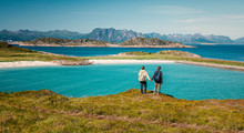 A Pair Of Girls Stands Holding Hands Against The Backdrop Of A Beautiful Landscape, Traveling To Norway On The Lofoten Islands