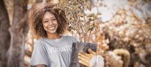 Portrait Of Female Volunteer Holding Plant