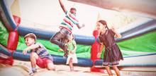 Friends Jumping On Bouncy Castle