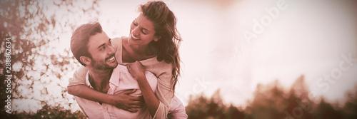Fotografie, Obraz  Young man piggybacking woman at farm during sunny day
