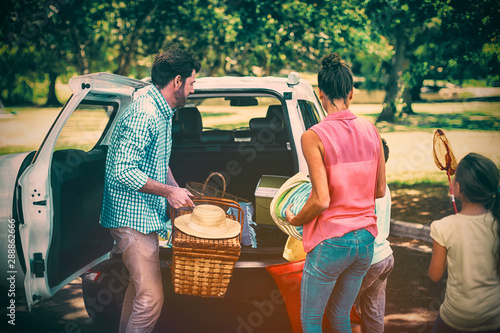 Family placing picnic items in car trunk