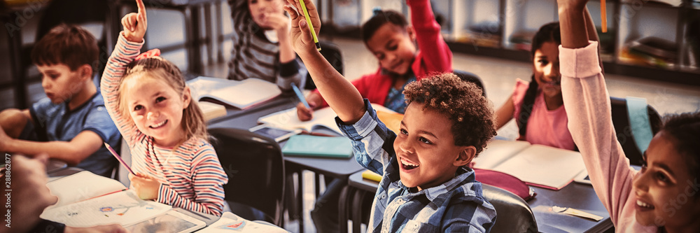 Fototapeta Schoolkids raising their hands in classroom