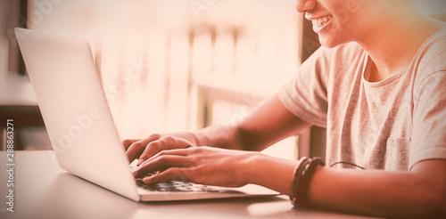 Happy schoolboy using laptop in classroom