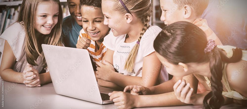 Fototapety, obrazy: School kids using laptop in library