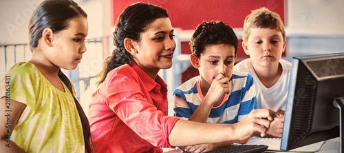 Female teacher teaching computer to children