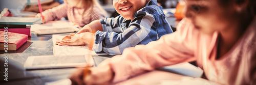 Portrait of smiling schoolboy doing his homework in classroom Wallpaper Mural