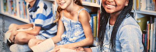 Portrait of children on floor with books in library