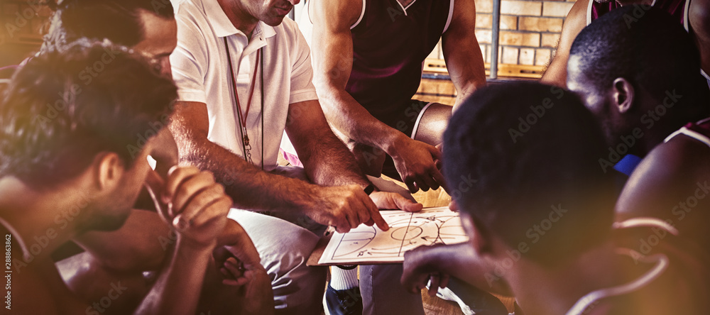 Fototapeta Coach explaining game plan to basketball players