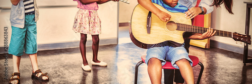 Teacher assisting a kids to play a musical instrument in classroom