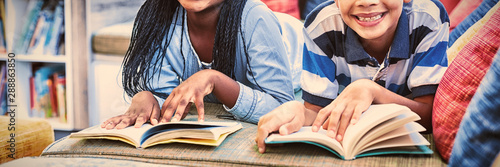 School kids lying on sofa and reading book
