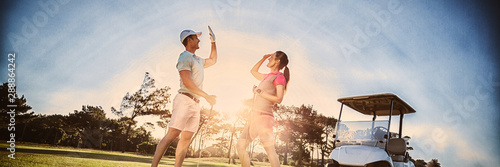 Full length of golf player couple giving high five