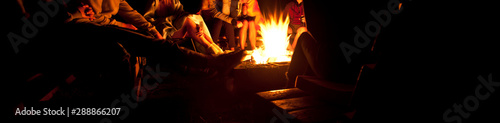 Obraz na plátne The group of friends are sitting near the bonfire in the night and talking about
