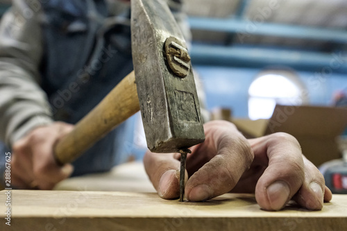 Fototapeta Carpenter hands with hammer and nail. Close up view. DIY concept