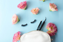 False Eye Lashes, Black Tweezers And Pink Flowers On Blue Background. Beauty Concept - Tools For Eyelash Extension.