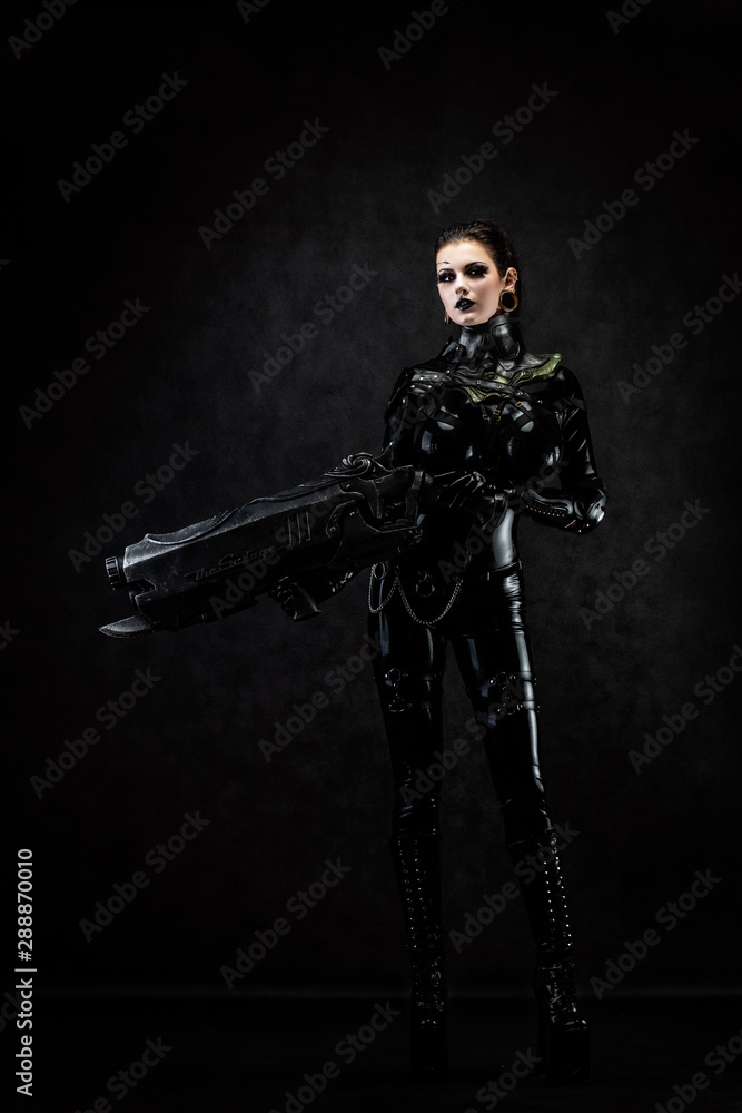 Fototapety, obrazy: Portrait of a young woman in latex jumpsuit holding a big futuristic weapon in her hands