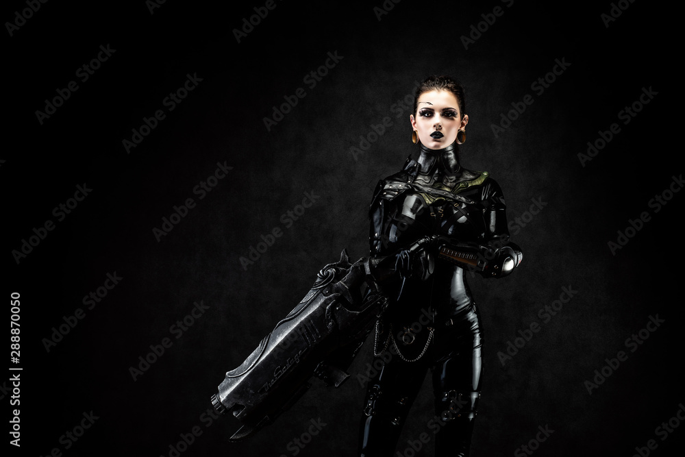 Fototapeta Portrait of a young woman in latex jumpsuit holding a big futuristic weapon in her hands