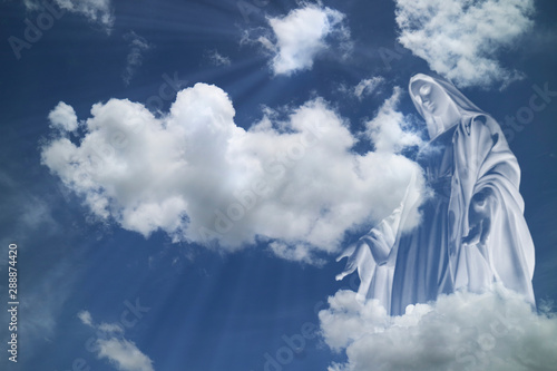 Fotografía Mary in white clouds with light ray from  heaven.