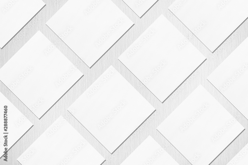 Fototapeta Many empty white square business card mockups with soft shadows lying diagonally on neutral light grey textured background. Flat lay, top view. Open composition.