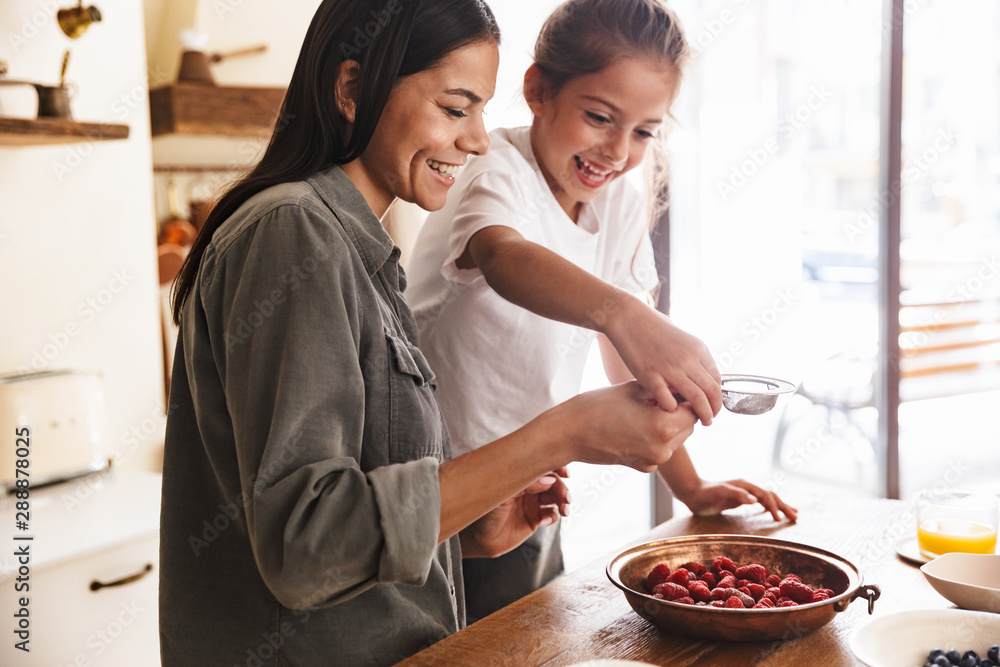 Fototapeta Image of positive family woman and her little daughter cooking together meal with raspberry at cozy apartment