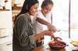 canvas print picture - Image of positive family woman and her little daughter cooking together meal with raspberry at cozy apartment