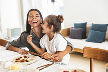 Image Of Cheerful Family Mother And Little Daughter Smiling And Eating Together While Having Breakfast At Home In Morning