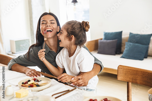 Image of cheerful family mother and little daughter smiling and eating together Wallpaper Mural