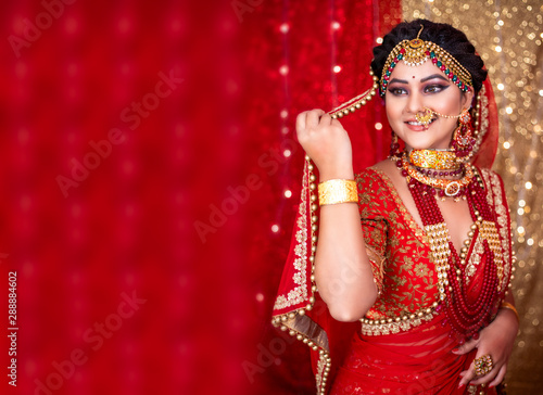 Canvas Print Portrait of an Indian bride wearing traditional red lehanga with gold jewelry an