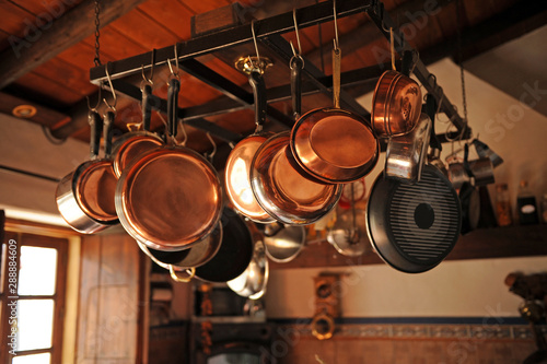Photo  Group of different pans hanging in the kitchen