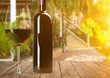 Leinwanddruck Bild Red wine in bottle and glass on wooden table