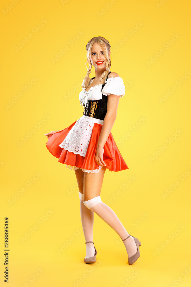 Fototapety, obrazy: Young sexy Oktoberfest girl waitress, wearing a traditional Bavarian or german dirndl isolated on yellow background. Full height photo.