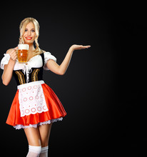 Smiling Sexy Oktoberfest Girl Waitress, Wearing A Traditional Bavarian Or German Dirndl, Serving Two Big Beer Mugs With Drink Isolated On Black Background. Woman Pointing To Looking Right.