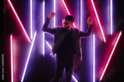 Hipster handsome man on the city streets being illuminated by neon signs Canvas Print