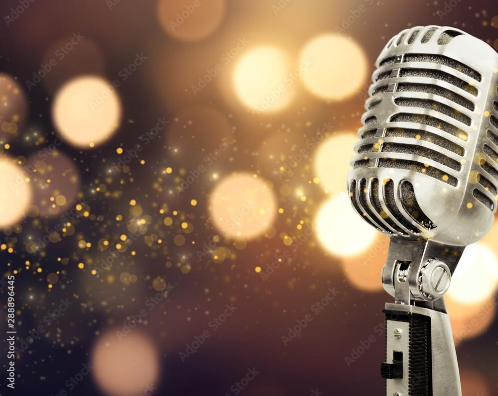 Fototapeta Retro style microphone on blurred background