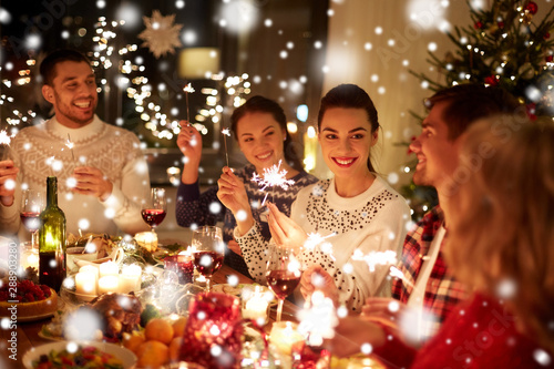 winter holidays and people concept - happy friends with sparklers celebrating christmas at home feast over snow - 288903280