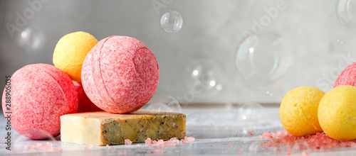 Colorful bath bombs, handmade soap and salt on the table, soap bubbles grey background. Home spa concept.