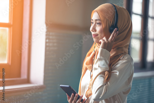 Fotomural  Portrait of a smiling young modern arabian woman holding mobile phone and listening the music to headphone