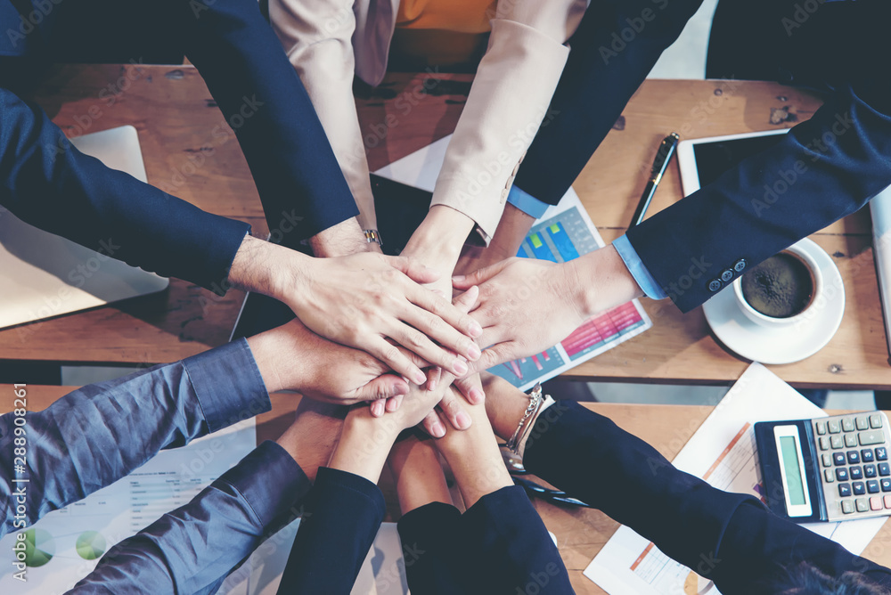 Fototapeta Teamwork Success.  Top view executive business people group team happy showing teamwork and joining hands after meeting partner business in office. Business  Concept.