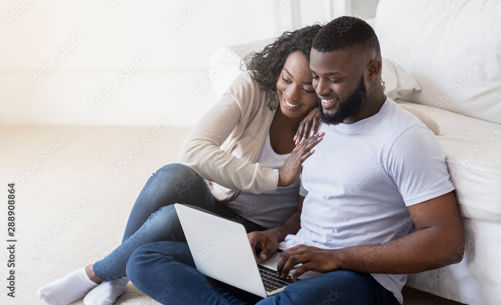Fototapeta African couple web surfing on laptop while sitting at home