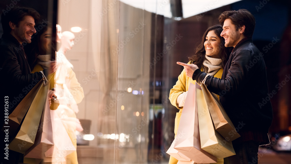 Fototapeta Couple looking at fashion store's window, shopping together